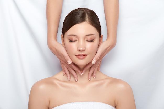 Ładna dziewczyna o masaż szyi, leżąc na białym