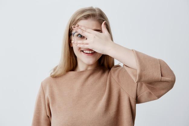 Ładna dziewczyna o nieśmiałym spojrzeniu zaglądającym przez palce, demonstrując nawet białe zęby. zawstydzona młoda śliczna kobieta z blond włosami chowającymi twarz za ręką uśmiecha się szeroko