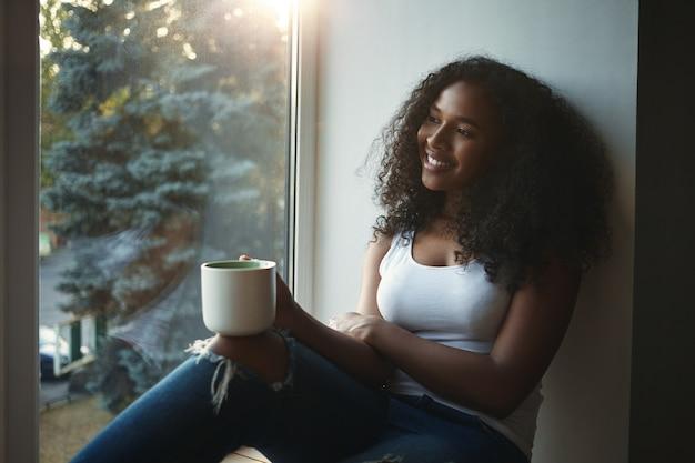 Ładna dziewczyna o wyglądzie mieszanej rasy trzymająca duży kubek i wyglądająca przez okno z promiennym, radosnym uśmiechem, obserwująca coś przyjemnego na zewnątrz, przy herbacie lub kawie. ludzie i styl życia