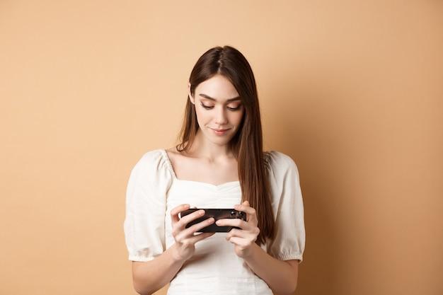 Ładna dziewczyna ogląda filmy na smartfonie trzymając telefon komórkowy poziomo i patrząc na ekran st...