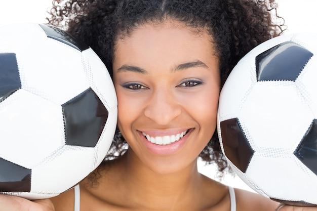 Ładna dziewczyna ono uśmiecha się przy kamery mienia futbolami z afro fryzurą