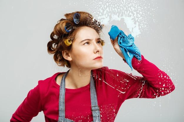 Ładna dziewczyna ostrożnie waha okna z niebieskim ręcznikiem