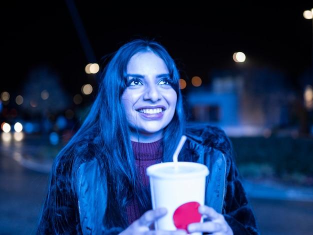 Ładna dziewczyna patrząc na niebieski ekran z sodą