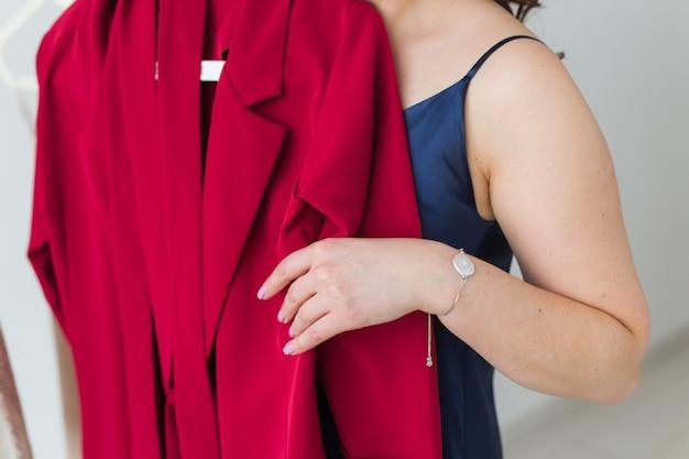 Ładna dziewczyna patrząc na sukienkę przy wyborze odpowiedniego. koncepcja mody, sprzedaży i sklepu.