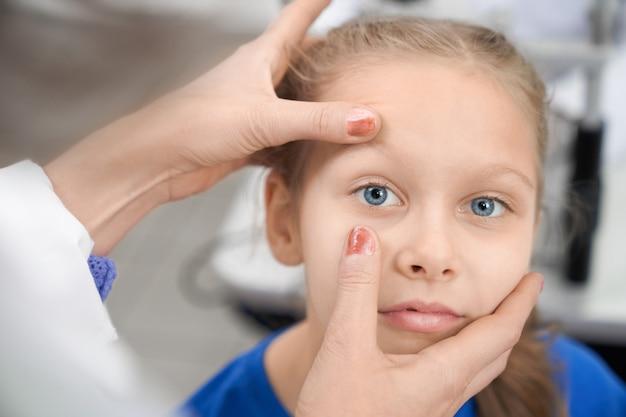 Ładna dziewczyna patrzeje kamerę podczas gdy okulista sprawdza wzrok