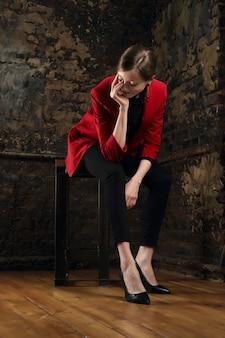 Ładna dziewczyna podpiera podbródek siedzi na krześle w pokoju z grunge ceglanymi ścianami i patrzeje w dół