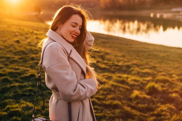 Ładna dziewczyna pozuje na zachodzie słońca nad jeziorem, ma radosny wyraz. ciepłe kolory zachodu słońca.