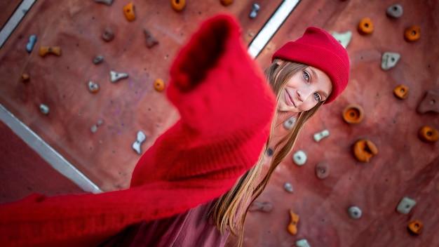 Ładna dziewczyna pozuje obok ściany wspinaczkowej