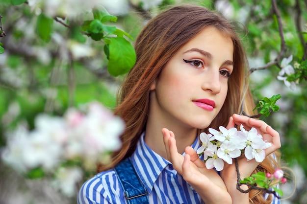 Ładna dziewczyna pozuje w ogrodzie w pobliżu drzewa kwiat z białymi kwiatami. wiosna