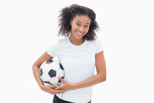 Ładna dziewczyna pozuje z jej futbolem