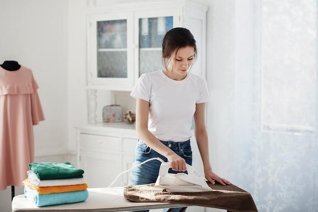 Ładna dziewczyna prasuje ubrania na desce, obok niej leży wielobarwny stos ubrań. w tle manekin w różowej sukience i białym bufecie.