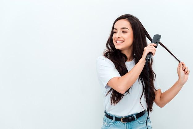 Ładna dziewczyna prostuje swoje piękne długie włosy