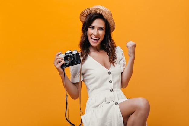 Ładna dziewczyna raduje się patrzy do aparatu na pomarańczowym tle. szczęśliwa kobieta w białej modnej sukience z dużymi przyciskami uśmiecha się.
