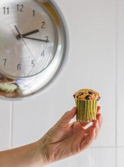 Ładna dziewczyna ręka biorąca pyszną czekoladową babeczkę podczas lunchu z metalowym zegarem w tle