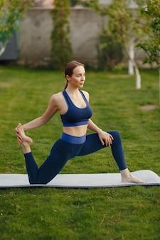 Ładna dziewczyna robi joga w letnim parku