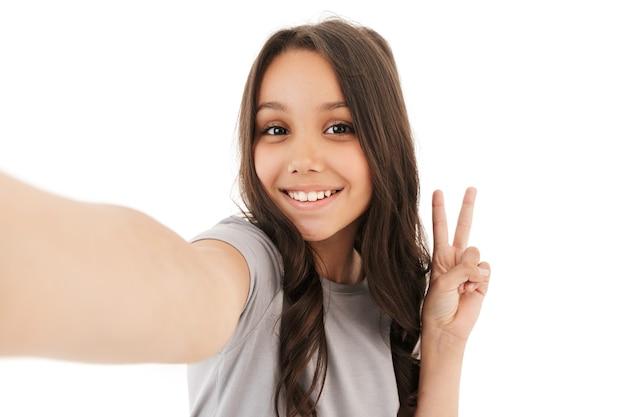 Ładna dziewczyna robi selfie patrząc na aparat pokazujący gest pokoju.