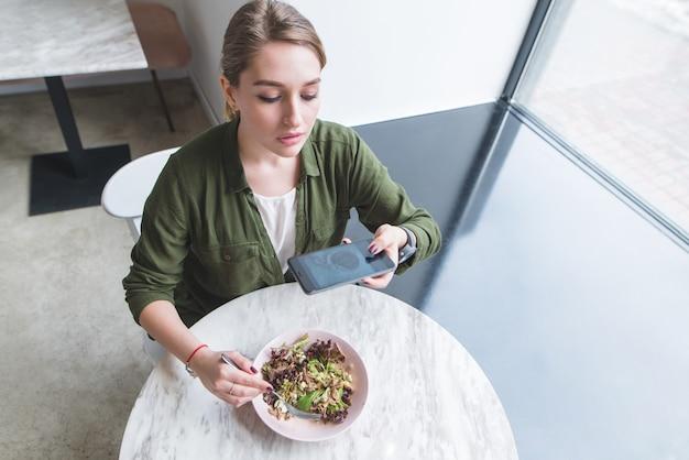 Ładna dziewczyna robi zdjęcie sałatki w restauracji. bloger podnosi jedzenie na stole w pobliżu okna