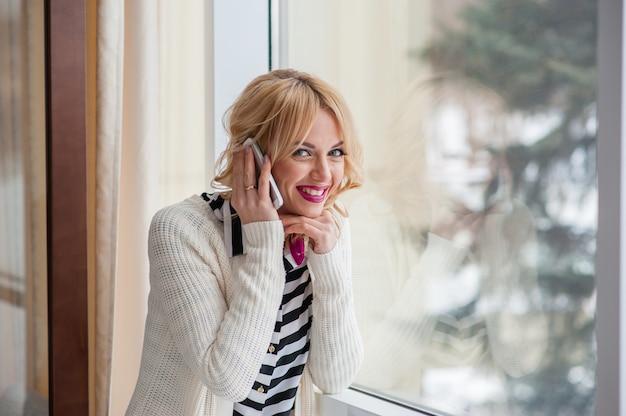 Ładna dziewczyna rozmawia przez telefon w pobliżu okna, blondynka