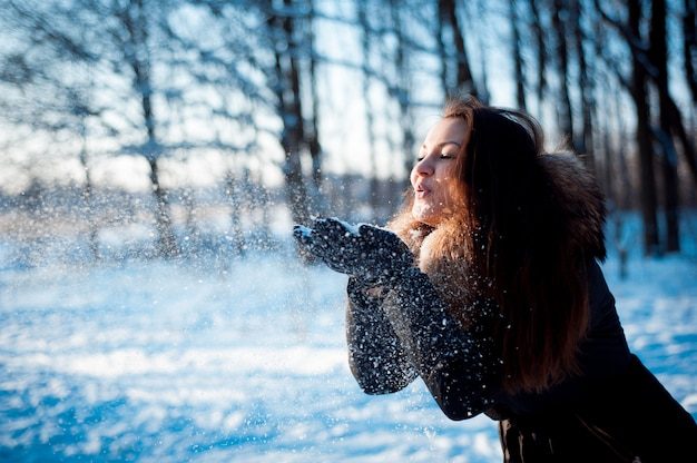 Ładna dziewczyna rzuca śnieg w winter park