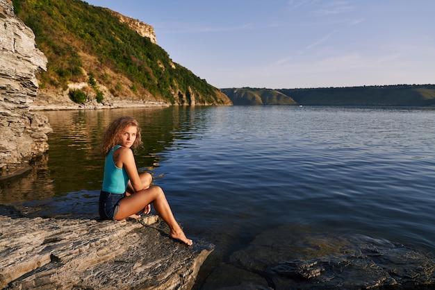 Ładna dziewczyna siedzi na brzegu jeziora.