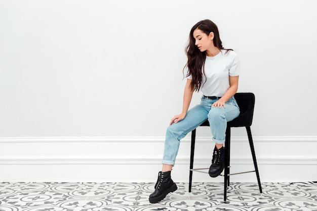 Ładna dziewczyna siedzi na krześle