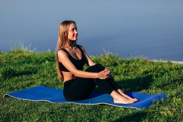 Ładna dziewczyna siedzi na matę do jogi, trzymając się za ręce jej zgięte nogi na zewnątrz.