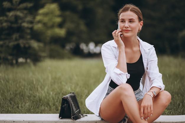 Ładna dziewczyna siedzi na ulicy i przy użyciu telefonu