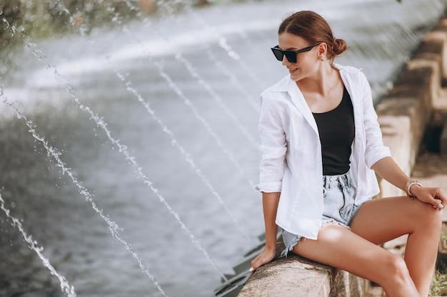 Ładna dziewczyna siedzi przy fontannach