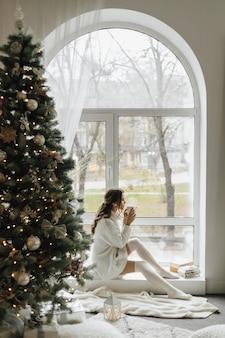 Ładna dziewczyna siedzi z filiżanką herbaty i kratę w pobliżu choinki