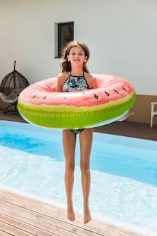 Ładna dziewczyna skacze w pobliżu basenu