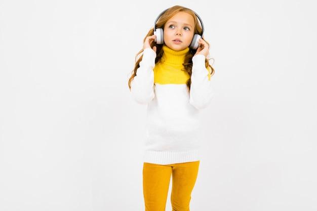 Ładna dziewczyna słucha muzyki w dużych białych hełmofonach