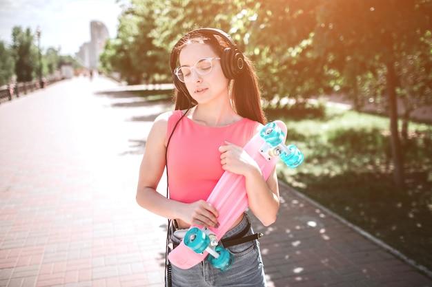Ładna dziewczyna stoi na ulicy i trzyma łyżwę w dłoniach