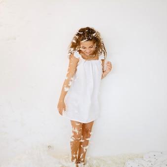 Ładna dziewczyna stoi pod spadającymi piórkami