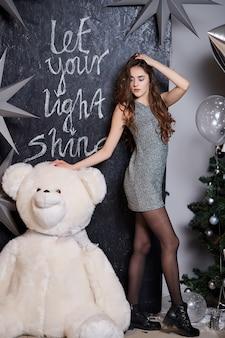 Ładna dziewczyna stojąca w pobliżu choinki i niedźwiedzia zabawka.
