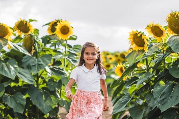 Ładna dziewczyna stojąca wśród słoneczników
