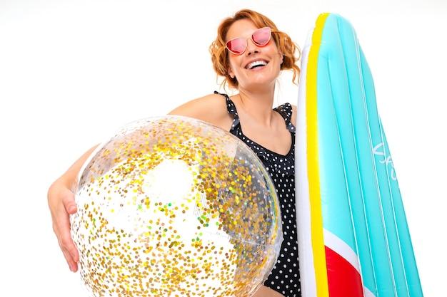 Ładna dziewczyna trzyma deskę surfingową i piłkę z błyszczy