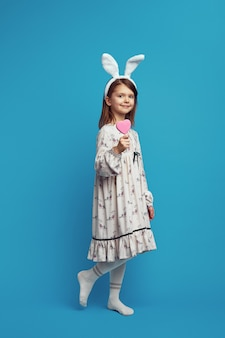 Ładna dziewczyna trzyma w ręku plik cookie w kształcie serca na niebieskiej ścianie