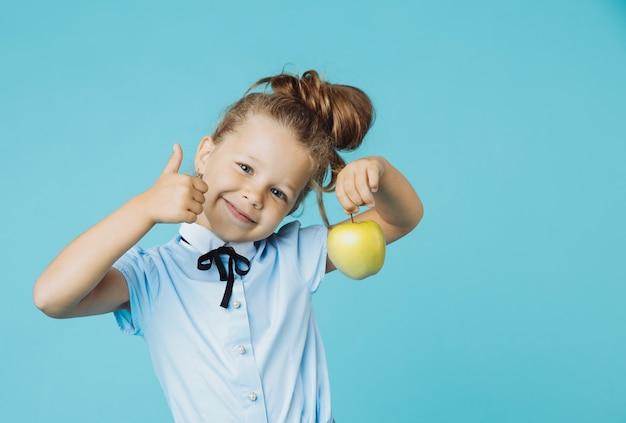 Ładna dziewczyna trzyma zielone jabłko na białym tle na niebieskiej ścianie.
