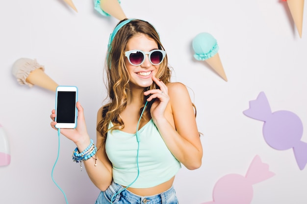 Ładna dziewczyna ubrana w akcesoria dotykające ręką twarzy i pokazujący telefon stojący na ścianie z cukierkami. portret szczęśliwa młoda kobieta w słuchawkach pozuje na ścianie ozdobionej słodyczami.