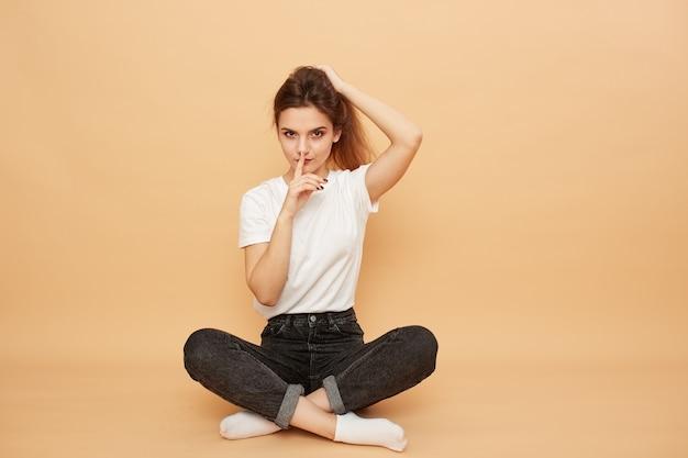 Ładna dziewczyna ubrana w białą koszulkę, dżinsy i białe skarpetki siedzi na podłodze z palcem na ustach na beżowym tle w studio.