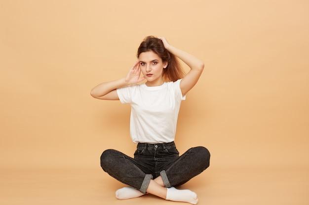 Ładna dziewczyna ubrana w białą koszulkę, dżinsy i białe skarpetki siedzi na podłodze z rękami na włosach na beżowym tle w studio.