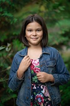 Ładna dziewczyna ubrana w kurtkę dżinsową pozuje na zewnątrz. nastoletni uśmiech brunetka moda