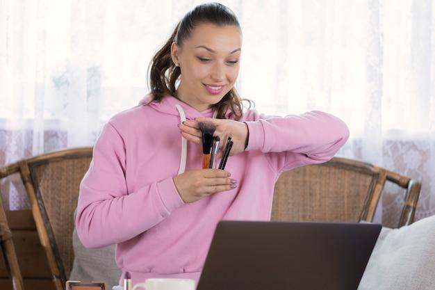 Ładna dziewczyna ubrana w różową bluzę z kapturem robi makijaż pokazujący frędzle do kamery laptopa