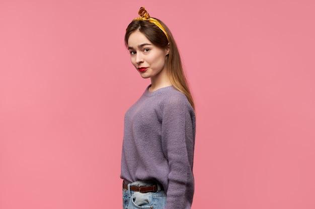 Ładna dziewczyna ubrana w stylowe ubrania pozuje przed różową ścianą studio