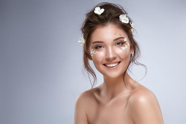 Ładna dziewczyna uśmiecha się do kamery z kwiatami pod oczami na szarym tle