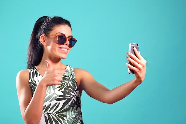 Ładna dziewczyna uśmiecha się szeroko podczas robienia selfie na swoim telefonie