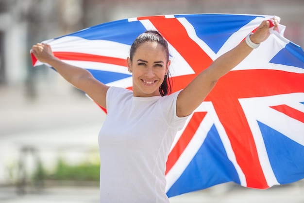 Ładna dziewczyna w białej koszulce trzyma za sobą flagę wielkiej brytanii, uśmiechając się do kamery.