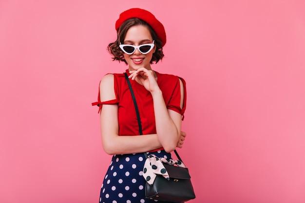 Ładna dziewczyna w białych okularach przeciwsłonecznych pozuje z delikatnie uśmiechem. piękna ciemnowłosa kobieta w francuskim berecie chłodzi.