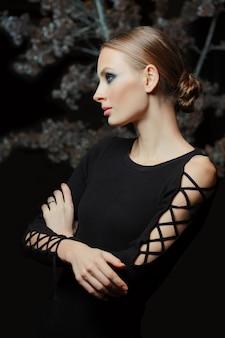 Ładna dziewczyna w czarnej sukience z dzianiny, wieczorowym makijażu i gładkich włosach pozujących na ciemności