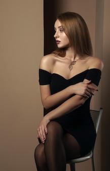 Ładna dziewczyna w czarnej sukni siedzi na białym stołku barowym. dziewczyna ze skrzyżowanymi nogami, patrząc w bok.